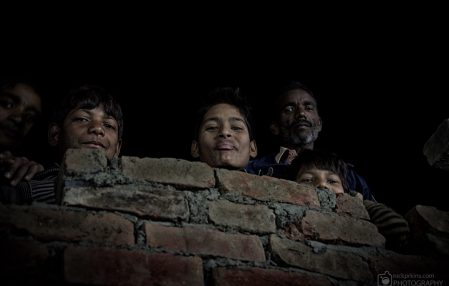 Indian family look over house wall